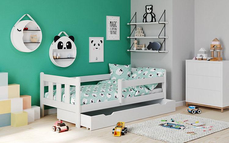 łóżko z barierką, komoda, półki i ozdoby ścienne w dziecięcym pokoju
