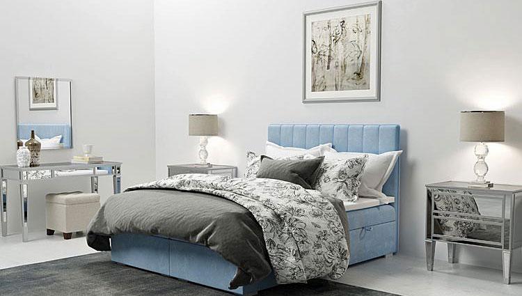 niebieskie tapicerowane łóżko kontynentalne we wnętrzy sypialni urządzonej w stylu glamour