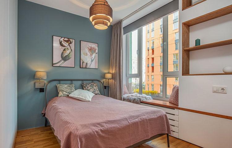 dwa obrazy na łóżkiem w sypialni