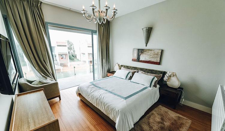sypialnia z obrazem umieszczonym na ścianie nad łóżkiem