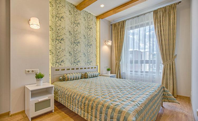 mała sypialnia z wytapetowaną ścianą.