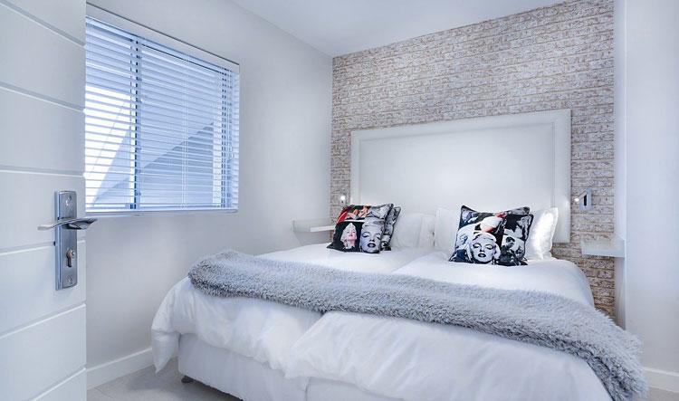tapeta na ścianie za łóżkiem w małej sypialni urządzonej w stylu skandynawskim